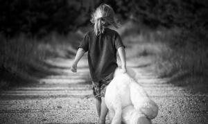 girl with teddy bear on path